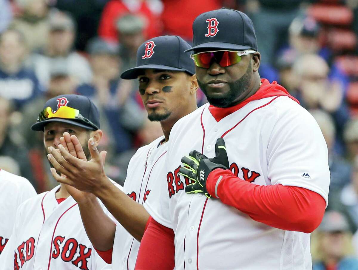 Boston Red Sox designated hitter David Ortiz pats his heart in response to cheering fans as teammate Xander Bogaerts applauds during player introductions before the home opener against the Baltimore Orioles at Fenway Park Monday.