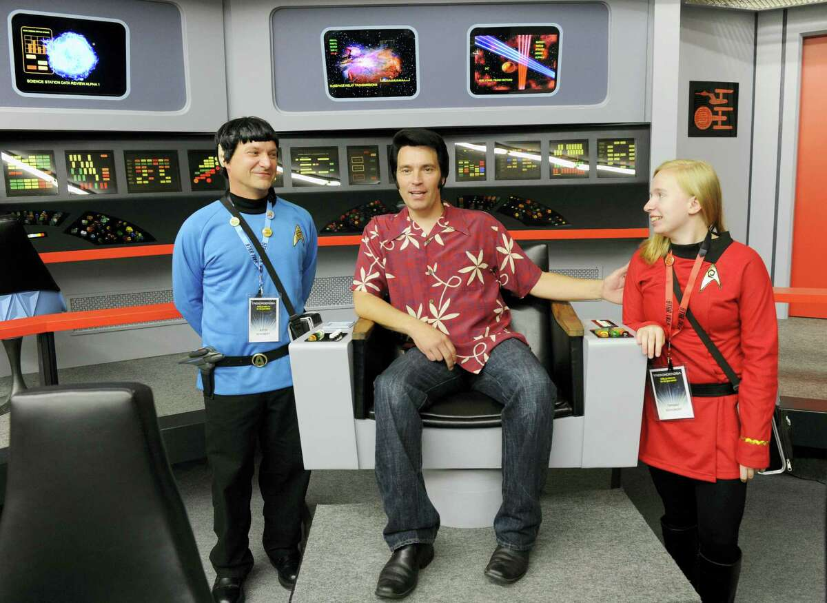 Keith Schubert of Peru, N.Y., left, dressed as Star Trek's Mr. Spock, and his daughter Tiffany Schubert, right, talk with James Cawley, center, during a tour of his replica of the starship Enterprise.