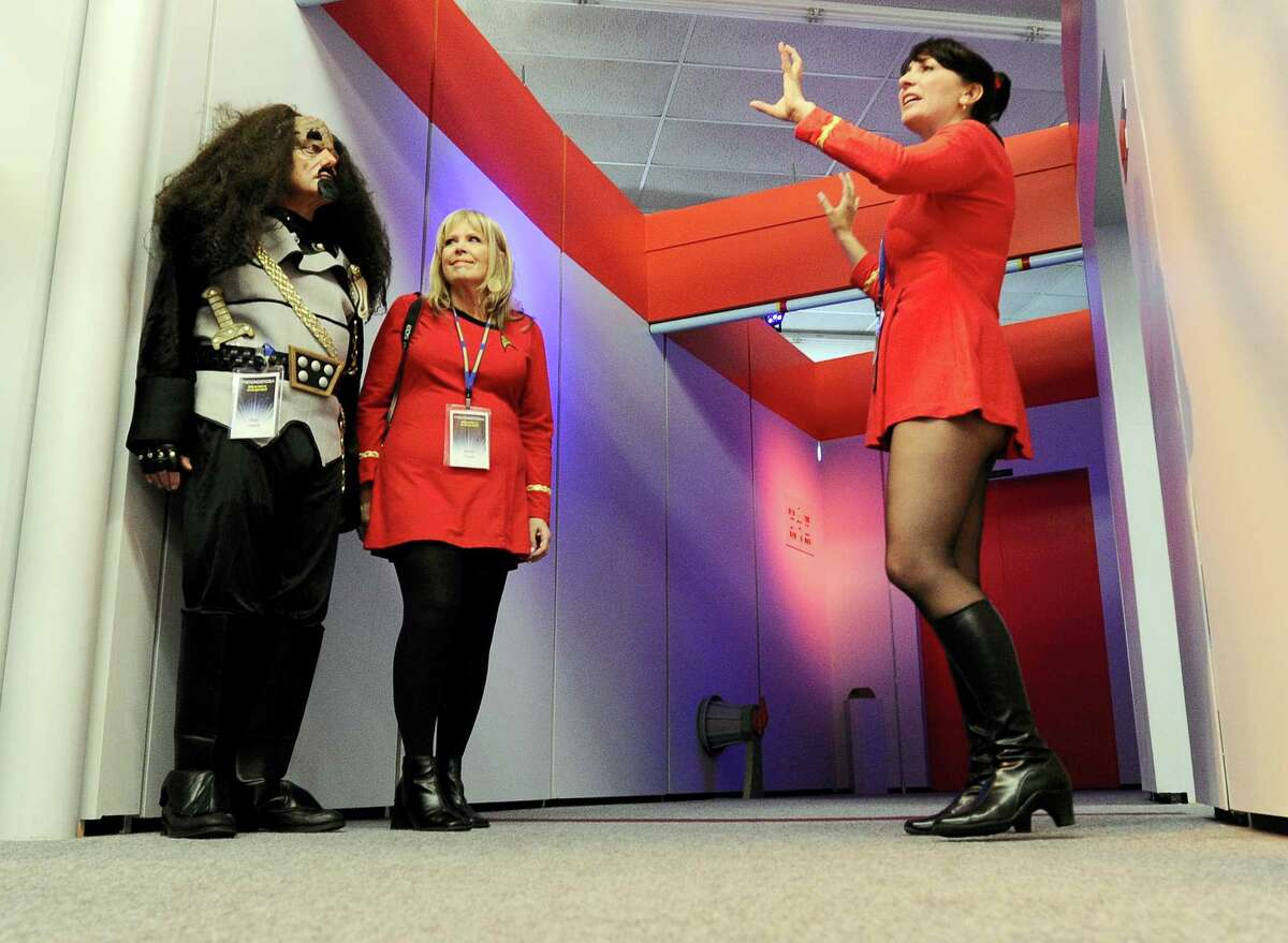 """Bud Fisher, left, and his wife, Kathy, center, of Enfield, Conn., dressed in """"Star Trek"""" costumes, take a guided tour of the replica starship Enterprise with tour guide Marybeth Ritkouski, right, of Pepperell, Mass., during the Trekonderoga festival in Ticonderoga, N.Y."""