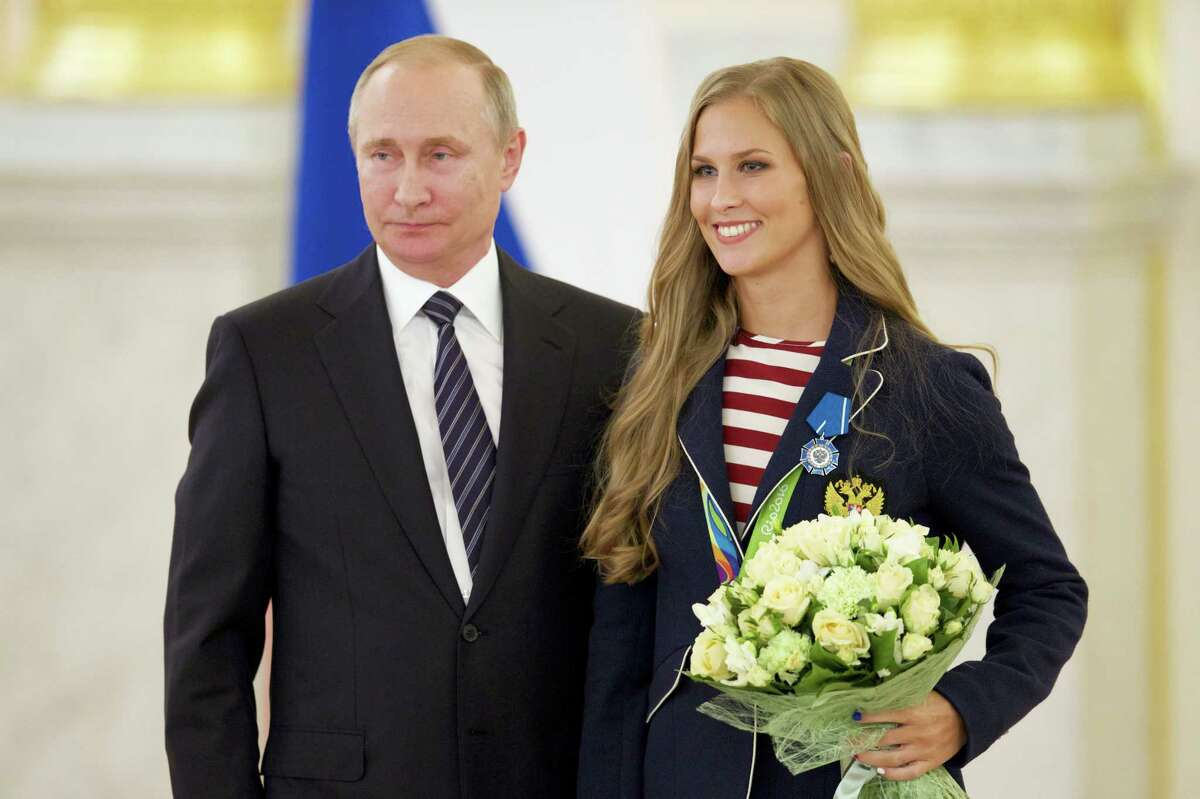 Russian President Vladimir Putin, left, poses with Alla Shishkina, who won her synchronised swimming team gold medal in Rio.