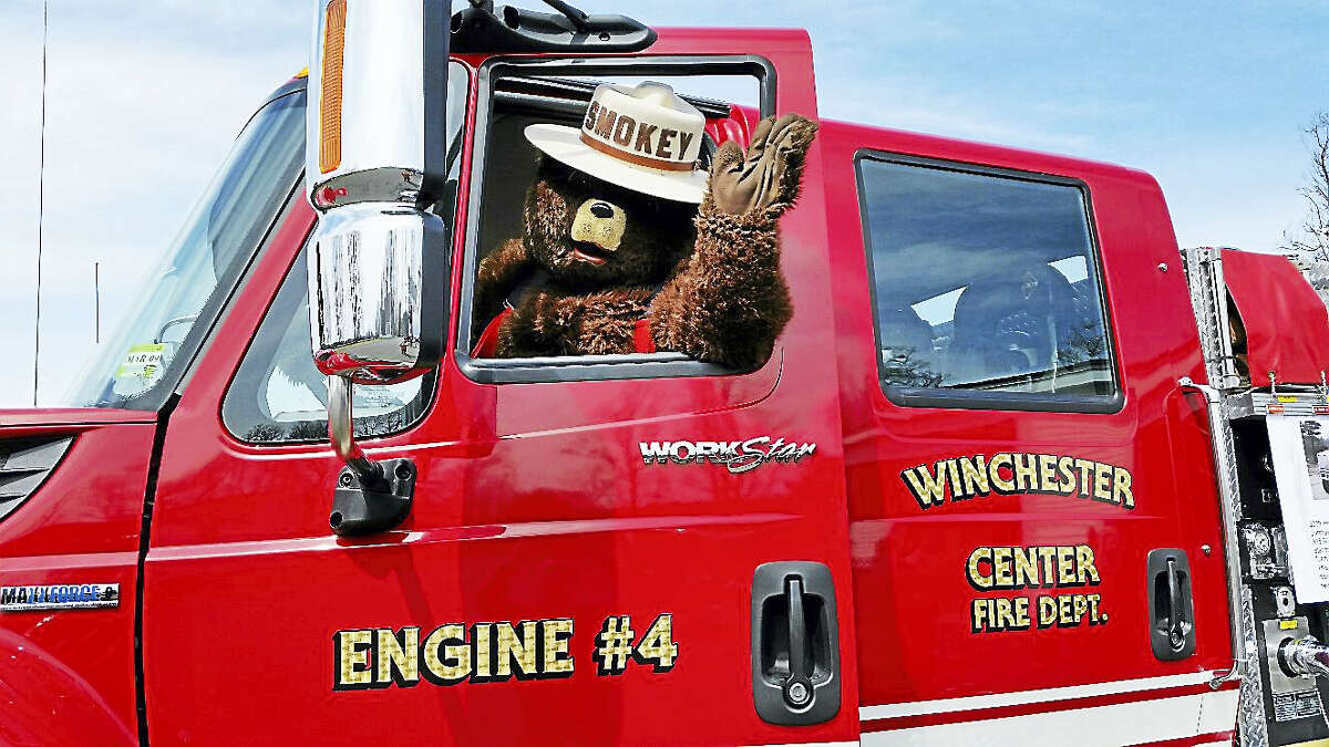 N.F. Ambery photo Firefighting mascot Smokey the Bear sat behind the wheel of a fire truck, preparing to receive visitors.