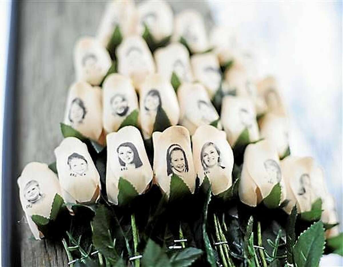 In this Jan. 14, 2013 file photo, white roses with the faces of victims of the Sandy Hook Elementary School shooting are attached to a telephone pole near the school on the one-month anniversary of the shooting.