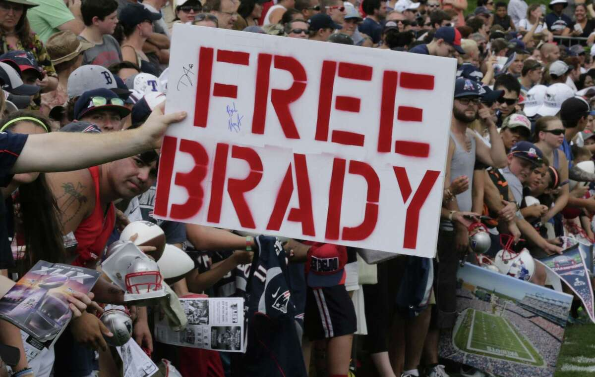 """A New England Patriots fan holds a """"Free Brady"""" sign during an NFL football training camp in Foxborough, Mass., Thursday, July 30, 2015. (AP Photo/Charles Krupa)"""