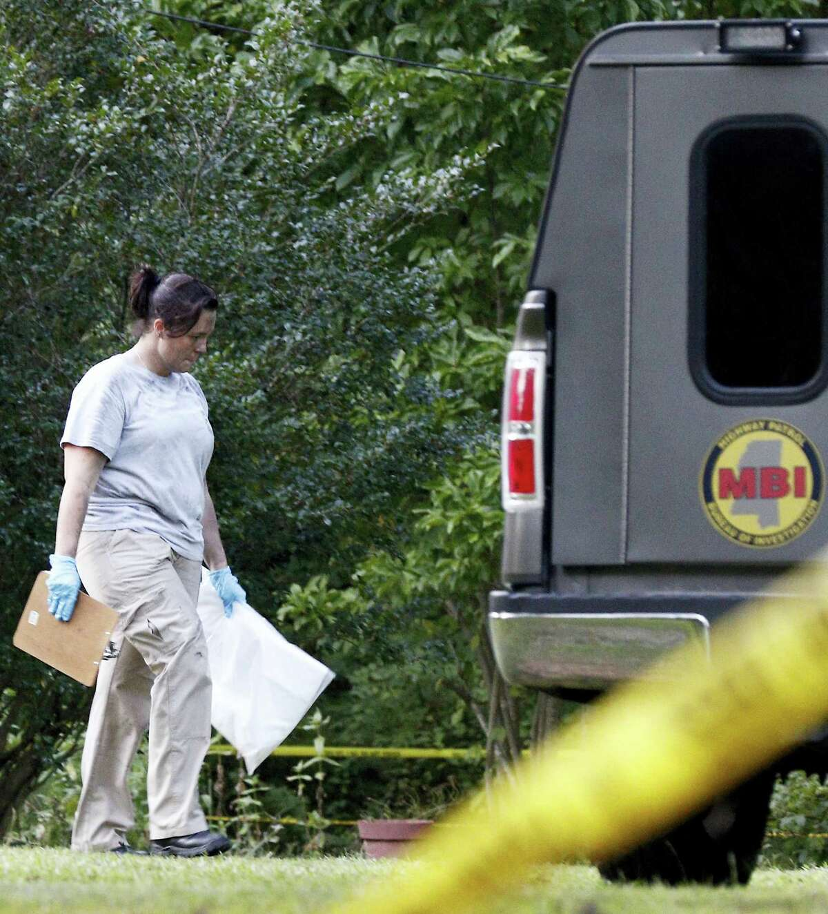 A Mississippi Bureau of Investigation agent takes a bag with evidence from the Durant, Miss., home of two slain Catholic nuns who worked as nurses at the Lexington Medical Clinic, to her vehicle, Thursday, Aug. 25, 2016. The clinic office manager and a Durant police officer discovered their bodies inside the house after both nuns did not report for work. Authorities said there were signs of a break-in and their vehicle was missing.