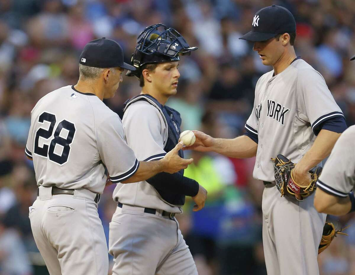New York Yankees relief pitcher Bryan Mitchell, right, hands the ball to manager Joe Girardi (28) catcher John Ryan Murphy, center, watches in the fifth inning of a baseball game against the Chicago White Sox in Chicago, Saturday, Aug. 1, 2015. (AP Photo/Jeff Haynes)