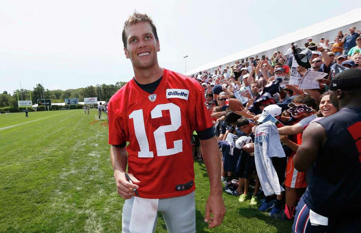 Patriots quarterback Tom Brady walks down the line of fans signing autographs Saturday in Foxborough, Mass.