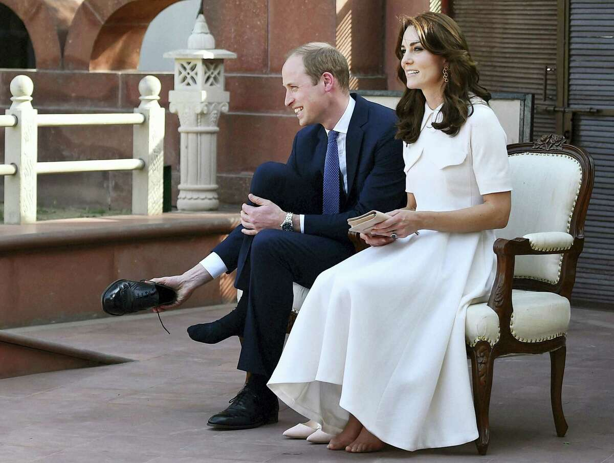 Britain's Prince William, and his wife Kate, the Duchess of Cambridge, remove their shoes before paying homage to Mahatma Gandhi during a visit to ''Gandhi Smriti'' in New Delhi, India on April 11, 2016.