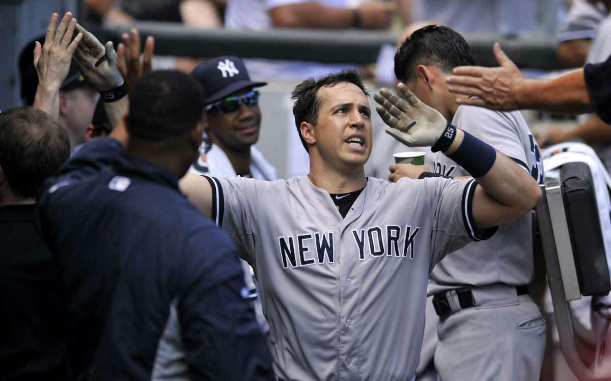 The Yankees' Mark Teixeria celebrates with teammates in the dugout after hitting a solo home run in the fifth inning Sunday.