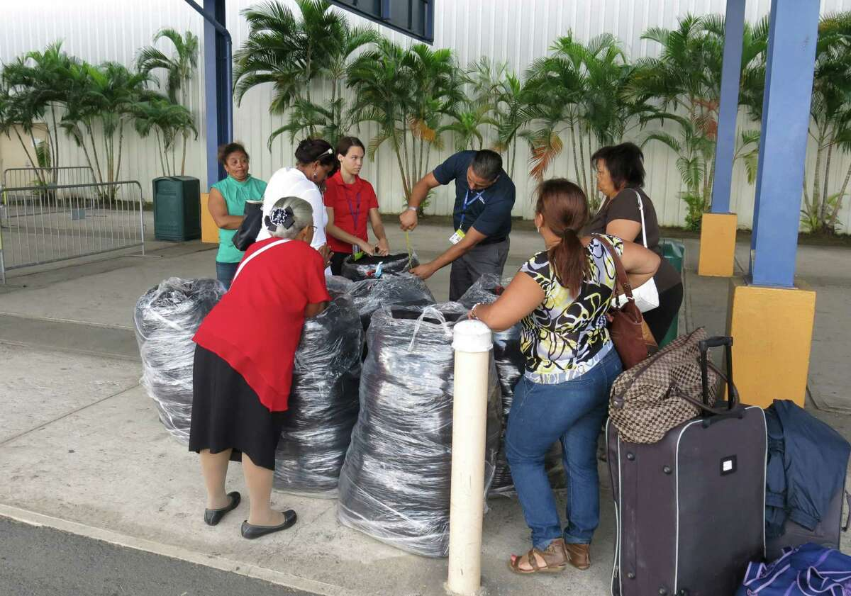 In this Jan. 22, 2016 photo, workers measure luggage size as passengers in San Juan, Puerto Rico wait to board a ferry headed for the Dominican Republic. A growing number of financially strapped Puerto Ricans are moving to the neighboring Caribbean country to open businesses and escape economic chaos that has scared away even many Dominican migrants.