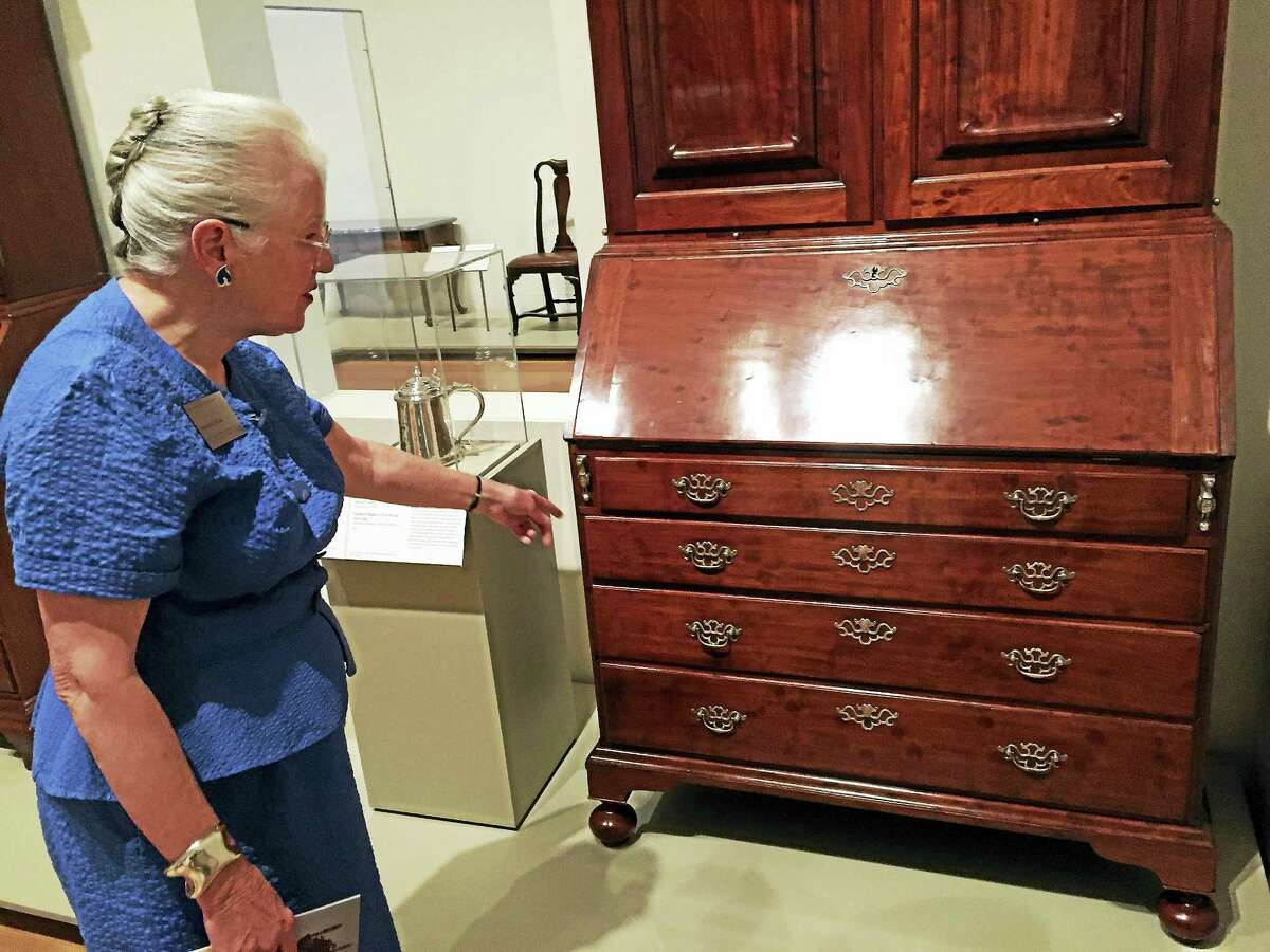 Curator Patricia Kane points to silver hardware done by Samuel Casey on a desk and bookcase by cabinetmaker Christopher Townsend from about 1745. Casey, the story goes, ran into money trouble and began counterfeiting silvery coins; he was slated to be hanged for it when friends sprung him from jail and he was never heard from again.