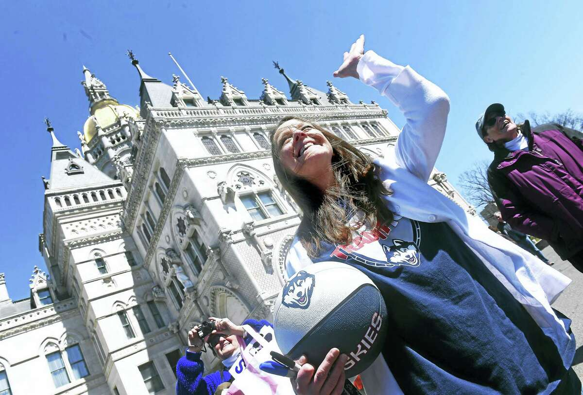 (Arnold Gold-New Haven Register) Nancy Beausoleil of Meriden waves to the UCONN Husky 2016 NCAA Women's Basketball National Championship team as the bus carrying the team prepares to start the victory parade at the State Capitol building in Hartford on 4/10/2016.
