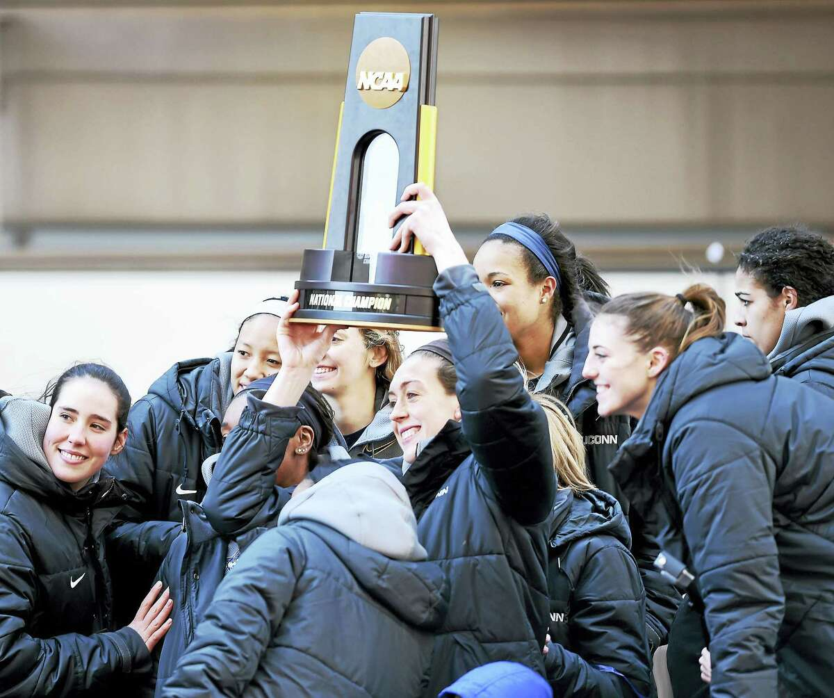 (Arnold Gold-New Haven Register) Breanna Stewart (center) holds the 2016 NCAA Women's Basketball National Championship trophy aloft while posing for a photograph with her teammates on top of a double decker bus during a victory rally in front of the XL Center in Hartford on 4/10/2016.
