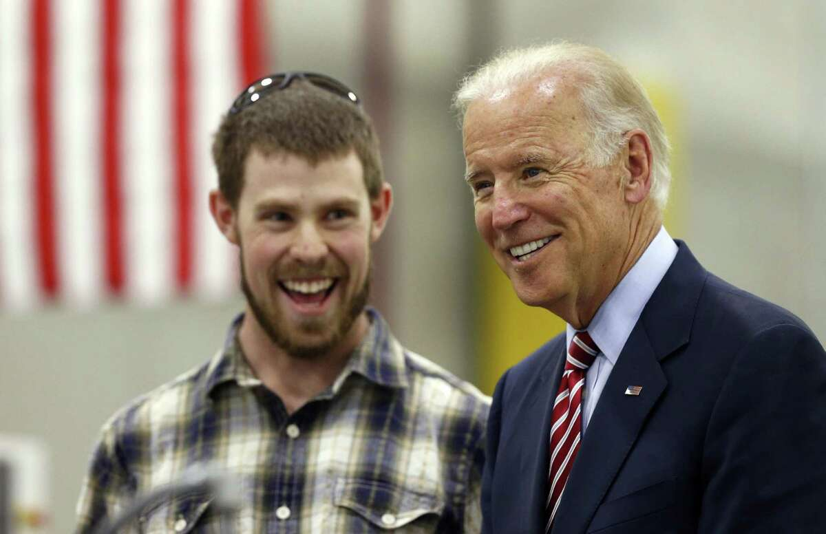 Vice President Joe Biden, right, laughs with advanced machinery student Luke Irick, during a tour of the Advanced Manufacturing Center at Community College of Denver on July 21, 2015. Biden traveled to Denver to speak about the administration's economic policies, and to participate in a roundtable discussion on what the White House views as a critical role played by partnerships between employers and community colleges.