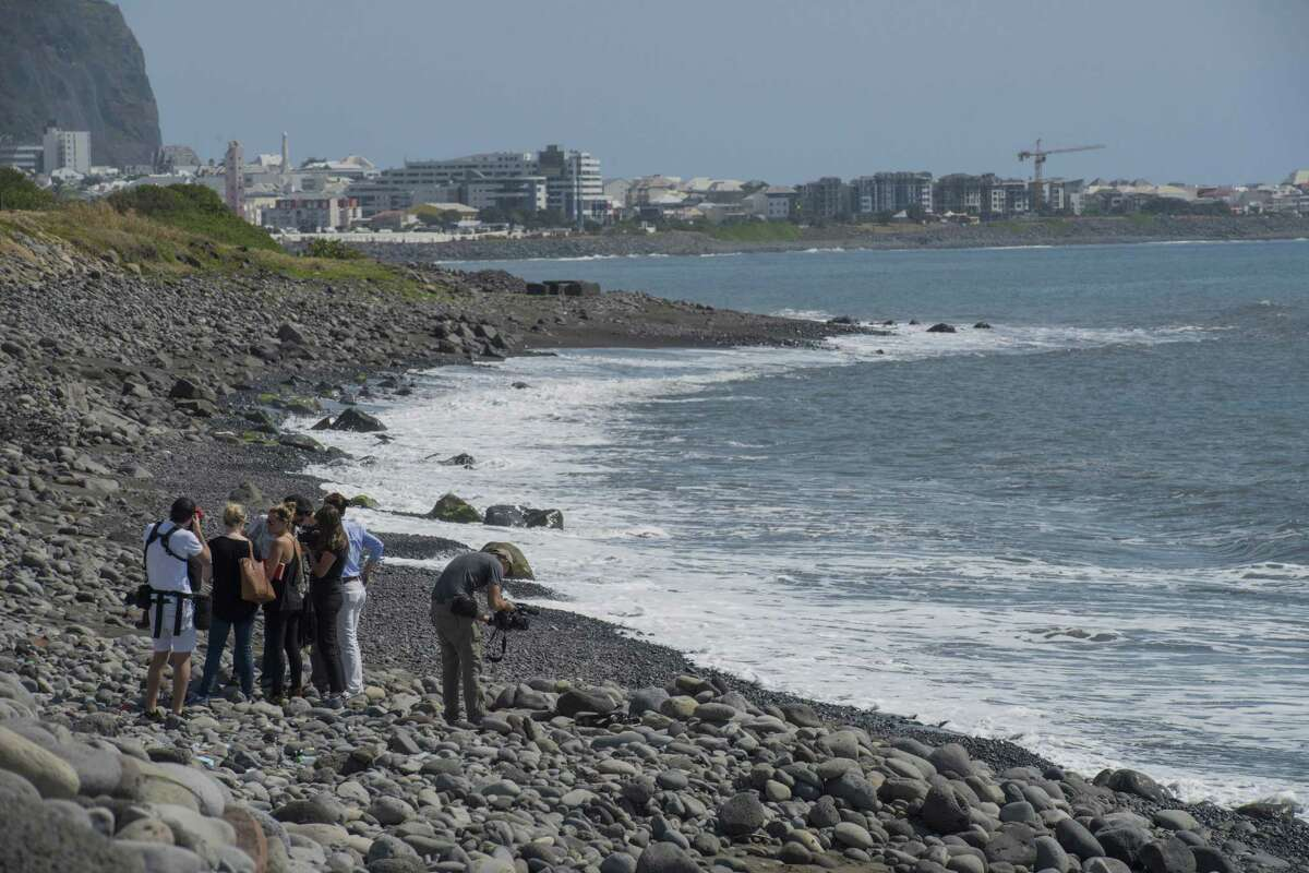 Workers for an association responsible for maintaining paths to Jamaica beach from being overgrown by shrubs, search the beach for possible additional airplane debris near the shore where an airplane wing part was washed up, in the early morning near to Saint-Denis on the north coast of the Indian Ocean island of Reunion on Aug. 2, 2015.