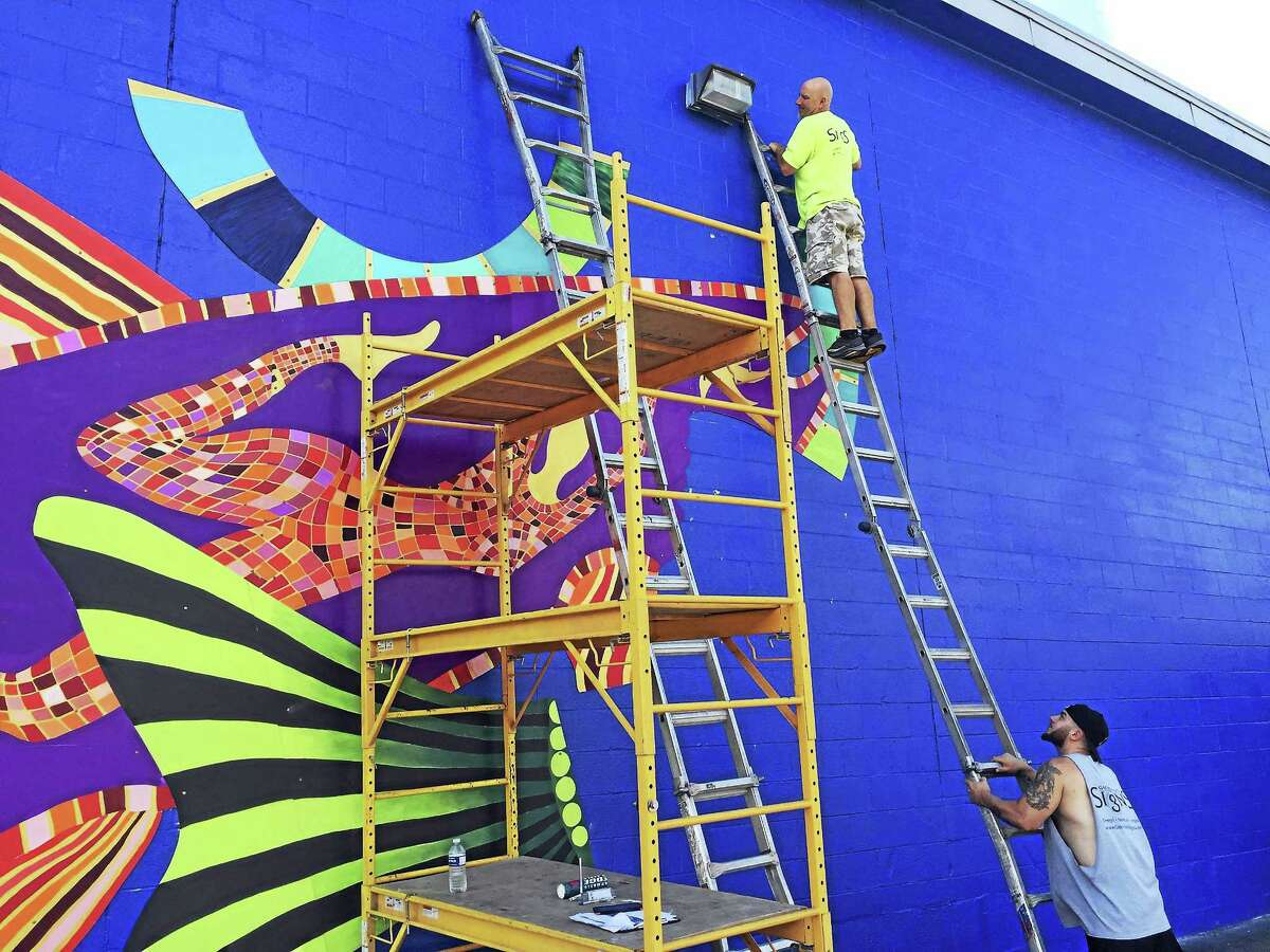 Ben Lambert - The Register CitizenA mural by Danielle Mailer is being installed on the rear wall of Staples in Torrington, overlooking the Naugatuck River.