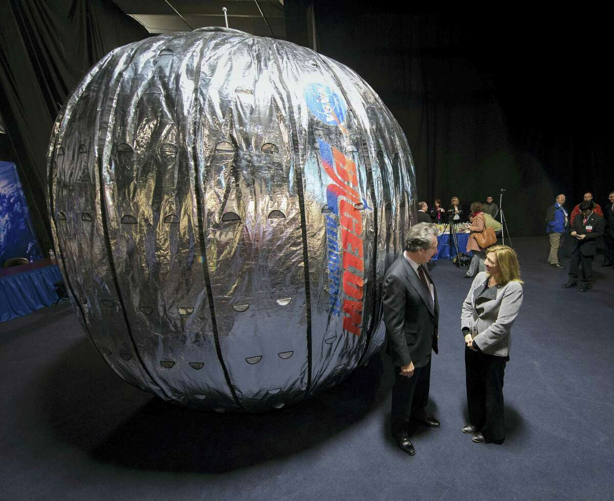 In this Jan. 16, 2013 photo made available by NASA, NASA Deputy Administrator Lori Garver and Robert T. Bigelow, president and founder of Bigelow Aerospace, stand next to the Bigelow Expandable Activity Module (BEAM) during a news conference in Las Vegas. It's a technology demonstration meant to pave the way for moon bases and Mars expeditions, as well as orbiting outposts catering to scientists and tourists.