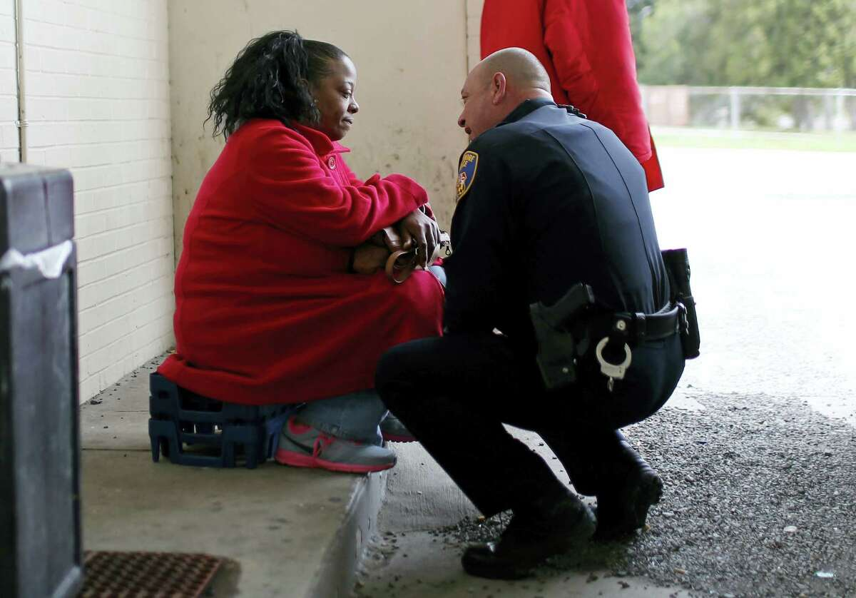 In this April 8, 2016 photo, Baltimore Police Department Officer Ken Hurst, right, consoles Rosa Brown, who was expressing suicidal thoughts following the recent death of her son, during his foot patrol in Baltimore. Hurst is one of 450 police officers who are part of a foot patrol program aimed at getting police officers out of their cars and onto the streets of Baltimore's most dangerous neighborhoods, not to make arrests but to make friends.