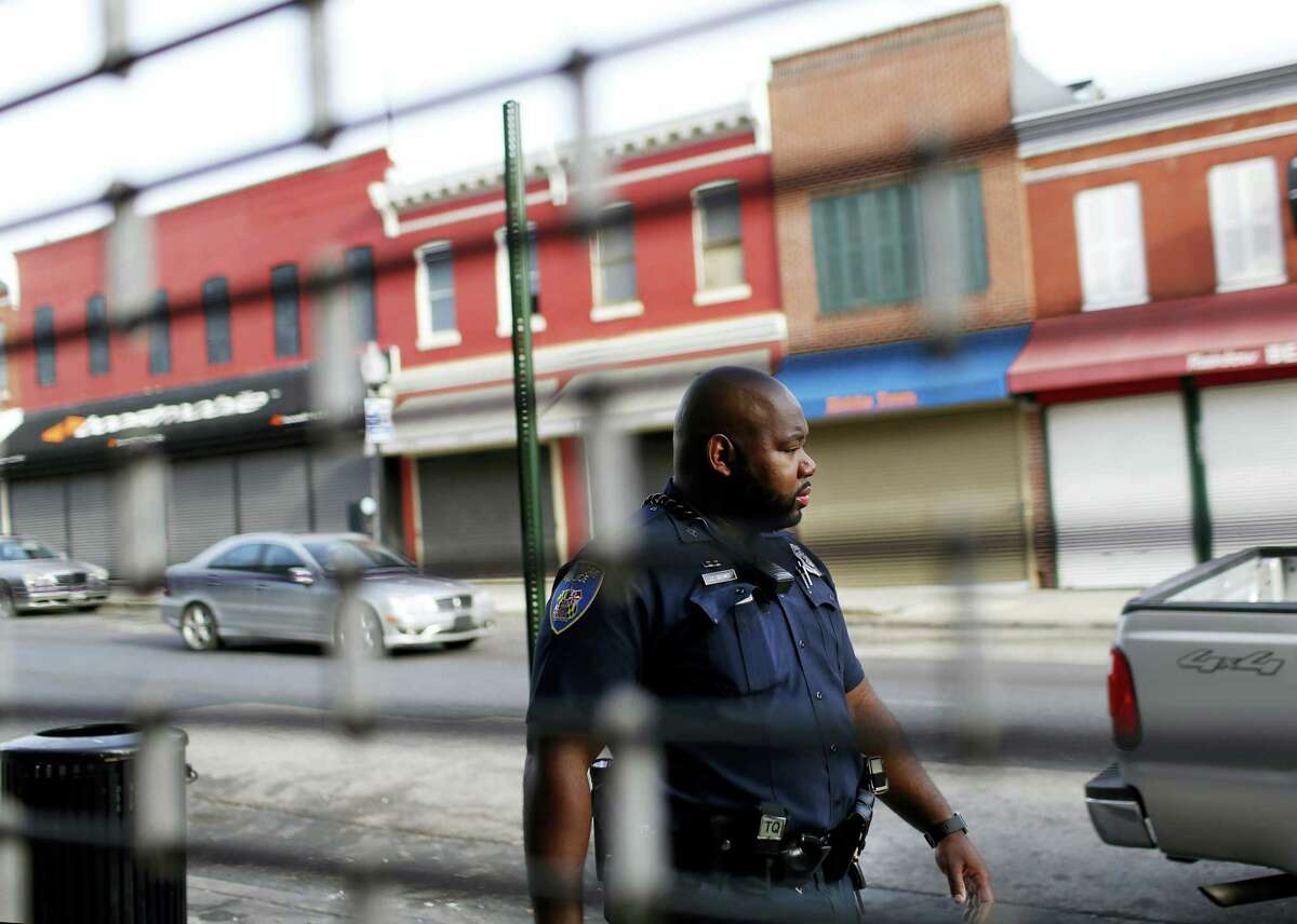 In this March 31, 2016 photo, Baltimore Police Department Officer Jordan Distance walks past businesses during a foot patrol in Baltimore. Part of the department's efforts have been putting more officers on foot patrol in poor, mostly black neighborhoods and encouraging beat cops to get more involved in the community.