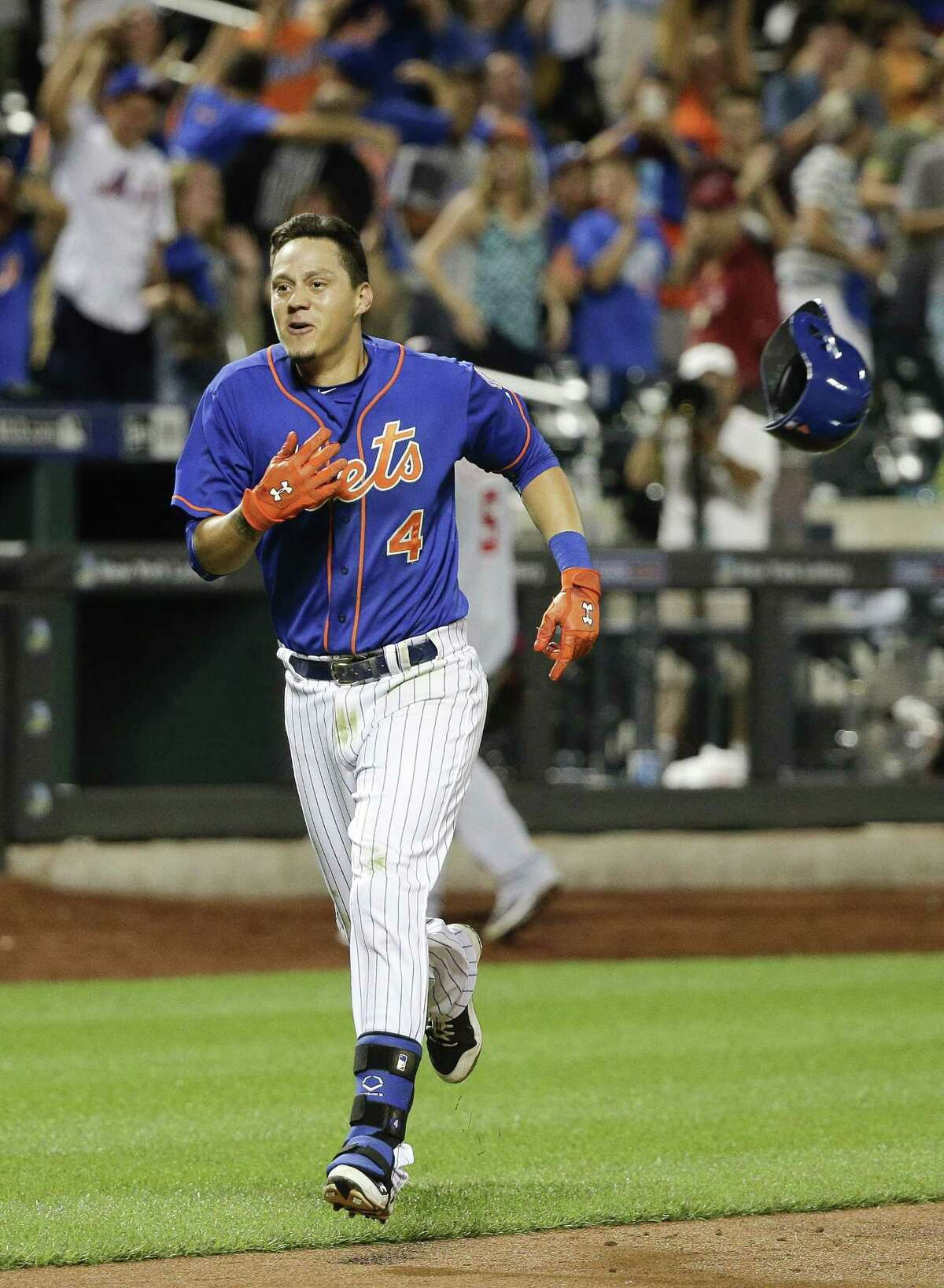The Mets' Wilmer Flores (4) tosses his helmet aside as he heads for home after hitting a walk-off solo home run in the 12th inning.