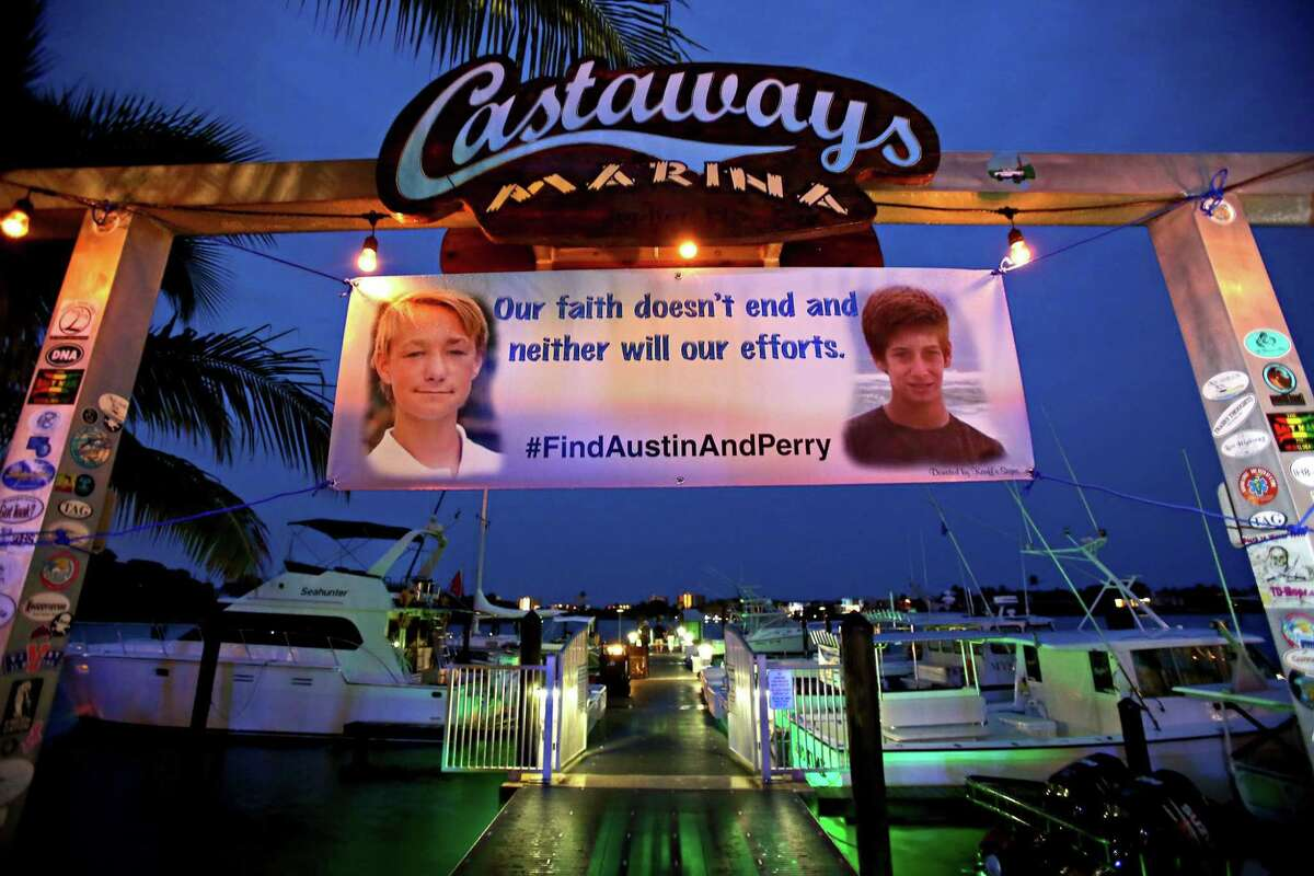 A banner hangs at the Castaways Marina with pictures of Austin Stephanos and Perry Cohen. After 8 days of searching the ocean, the U.S. Coast Guard ended their search for the boys. Friends and relatives attended a fundraiser at the Square Grouper, Friday in Jupiter, Fla.