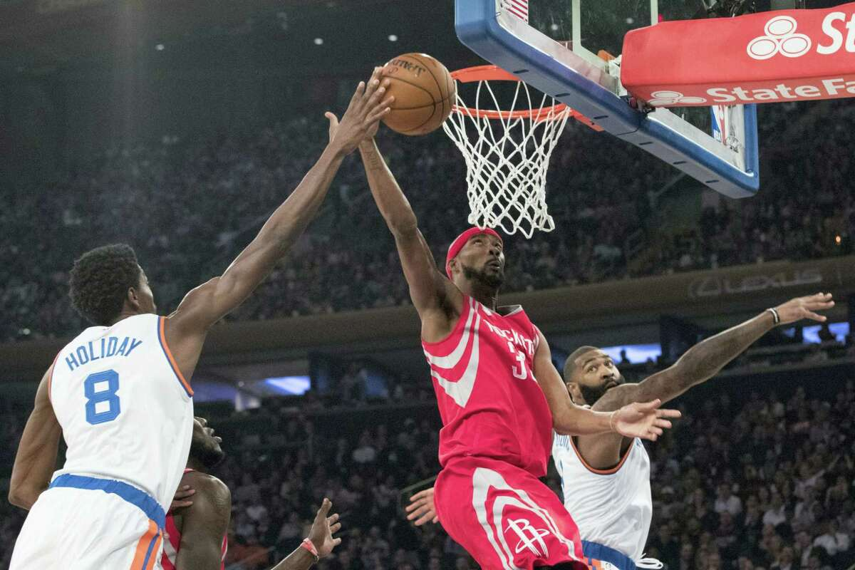 Houston Rockets forward Corey Brewer (33) goes to the basket past New York Knicks guards Justin Holiday (8) and Brandon Jennings during the first half at Madison Square Garden in New York. The Rockets won 118-99.