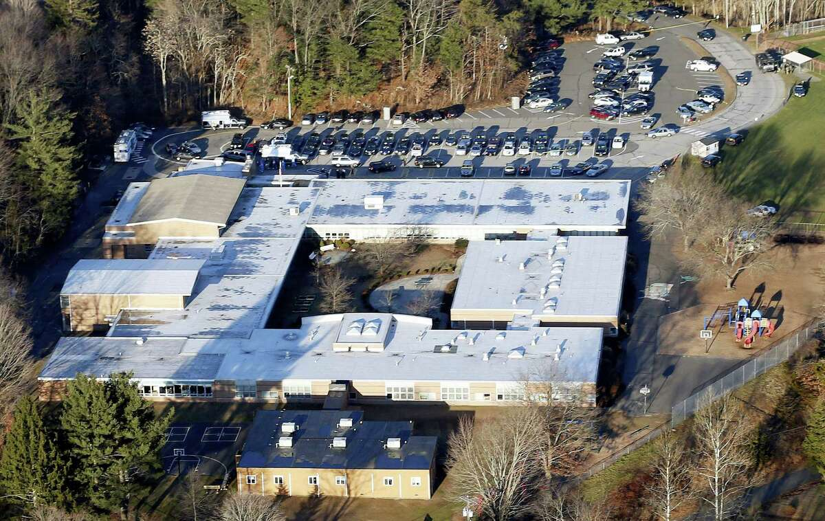 This Dec. 14, 2012, aerial file photo shows Sandy Hook Elementary School in Newtown, Conn. Contractors demolishing Sandy Hook Elementary School are being required to sign confidentiality agreements forbidding public discussion of the site, photographs or disclosure of any information about the building where 26 people were fatally shot in December 2012.
