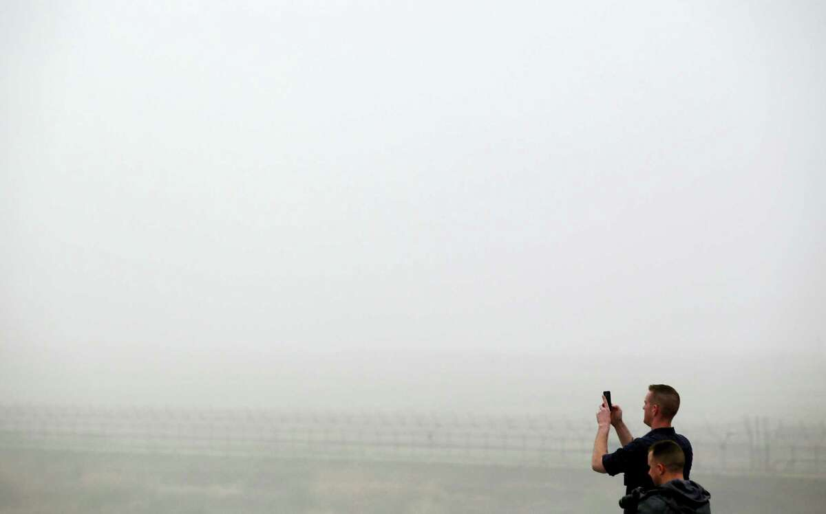 Visitors take photos on a foggy day at the Imjingak Pavilion near the border village of the Panmunjom in Paju, South Korea, Saturday, April 9, 2016. North Korea said Saturday it has successfully tested a new intercontinental ballistic rocket engine that will give it the ability to stage nuclear strikes on the United States.