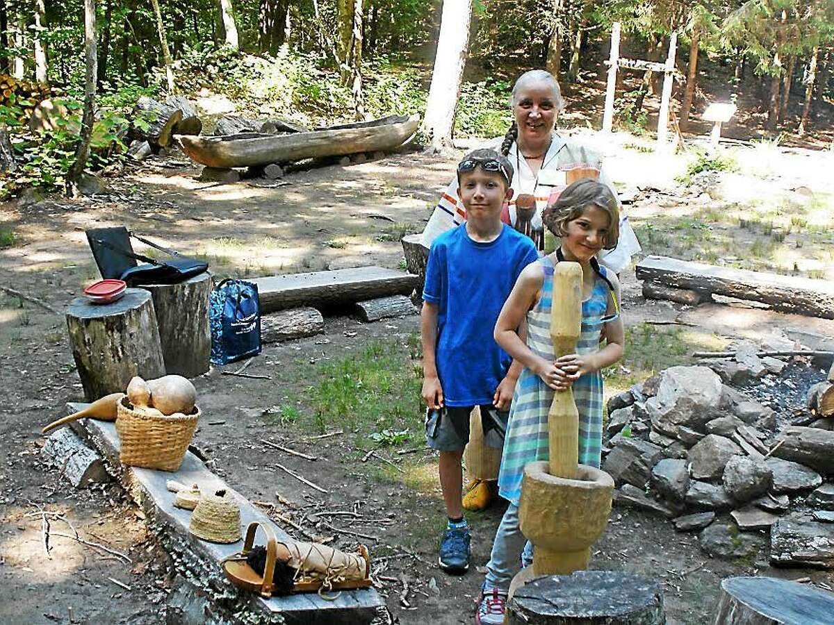 Stephen Underwood — Special to the Register CITIZEN Darlene Kascak, museum assistant and educator, shows Natty Key, 8, and Sassy Key, 9, how to grind corn in the traditional Native American way.