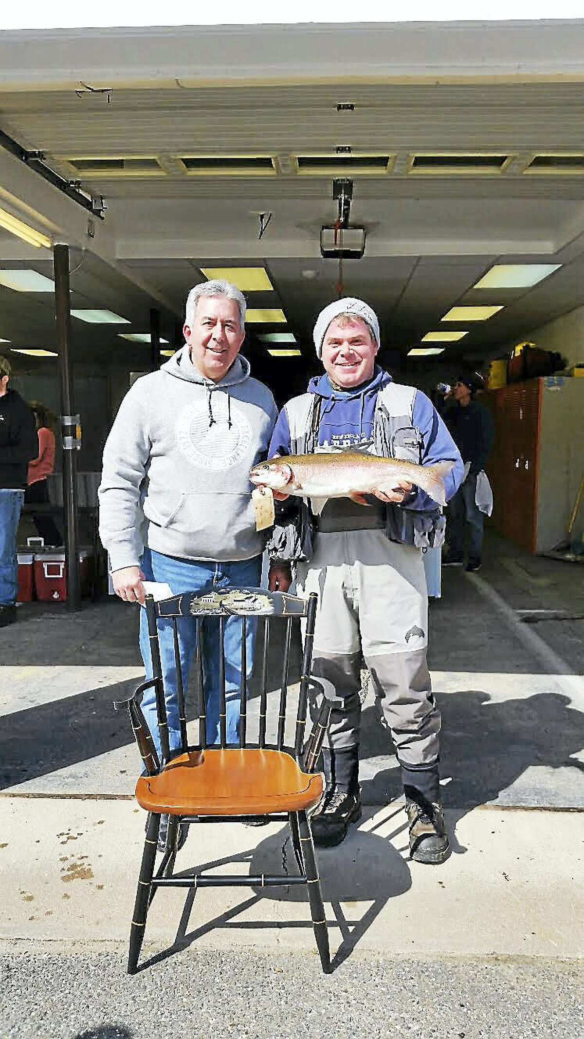Brandon D'Angelo, 34, of Barkhamsted shows off his 24 ½-inch rainbow trout and his prize, a customized wooden Hitchcock chair, along with his father, Gary D'Angelo, of Winsted at the 67th annual Riverton Fishing Derby on the West branch of the Farmington River near the Old Riverton Inn at 436 E. River Road in Riverton Saturday.