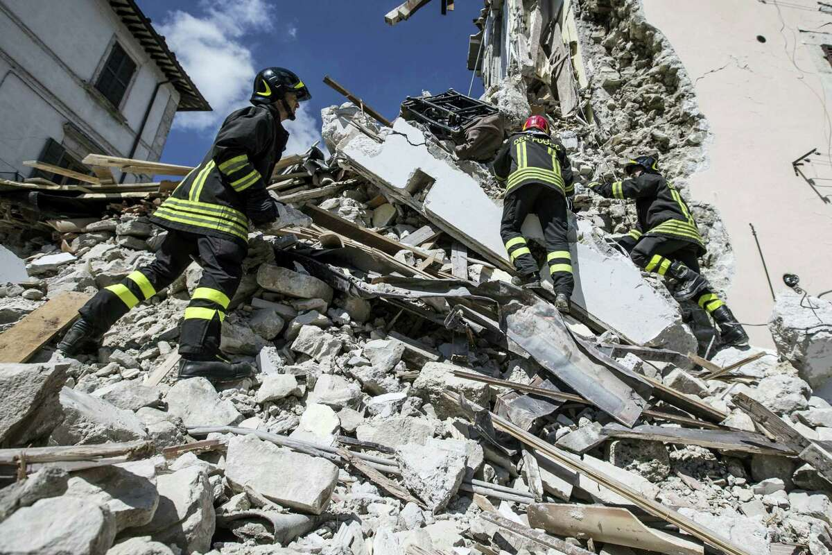 Firefighters search through debris in Arquata, central Italy, Thursday, Aug. 25, 2016, where a 6.1 earthquake struck just after 3:30 a.m., Wednesday. Rescue crews raced against time Thursday looking for survivors from the earthquake that leveled three towns in central Italy, but the death toll rose to 241 and Italy once again anguished over how to secure its towns and cities, new and old, built on seismic lands.