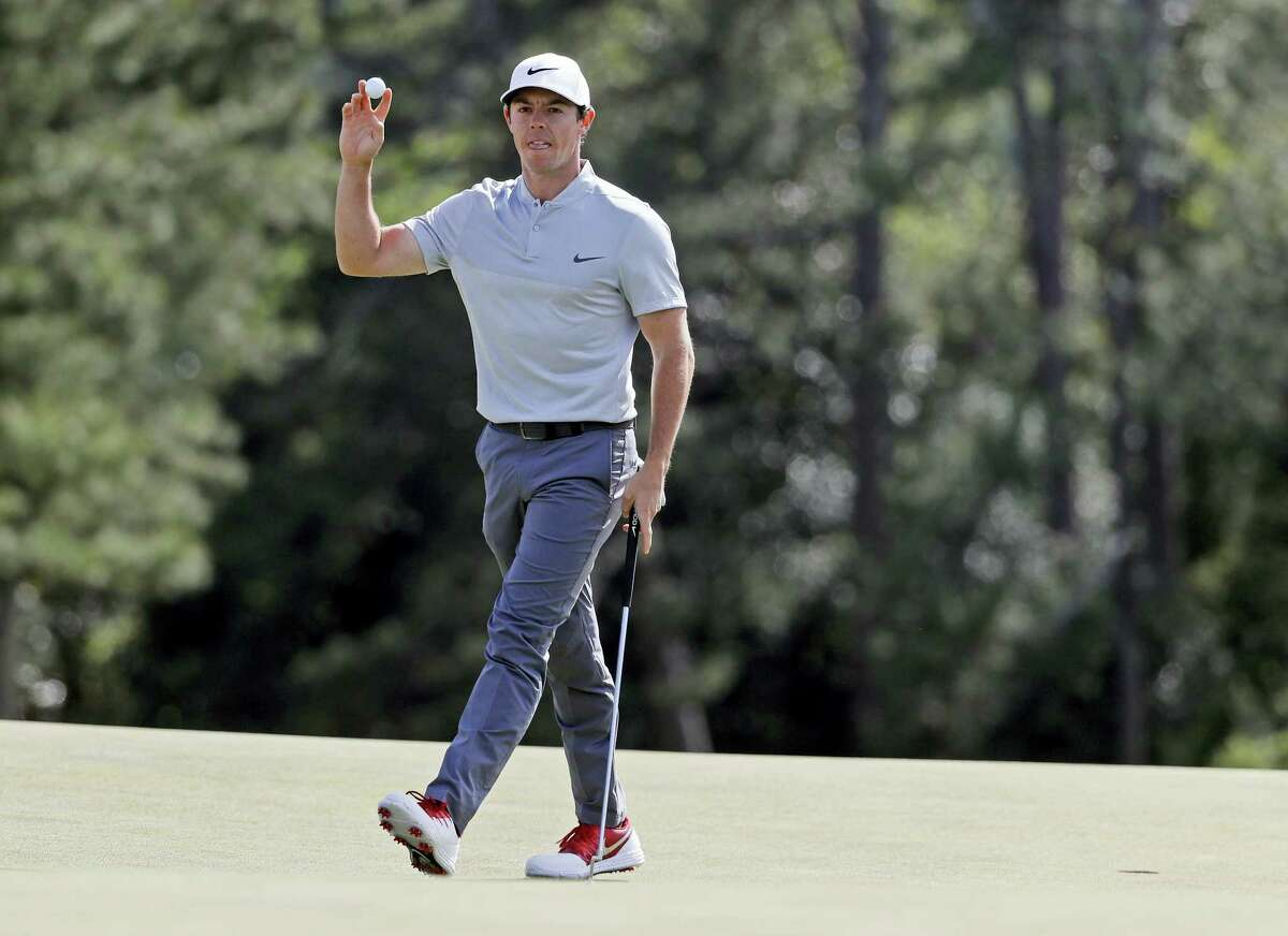 Rory McIlroy holds up his ball after putting out on the 18th hole.