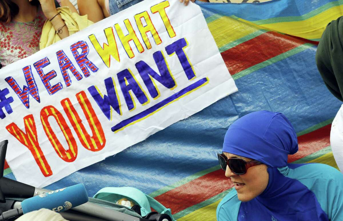 """An activist protests outside the French embassy during, the """"wear what you want beach party"""" in London Thursday. The protest is against the French authorities clampdown on Muslim women wearing burkinis on the beach."""