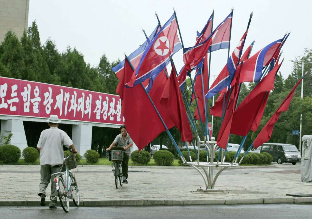 """A North Korean rides a bicycle past national flags flown to mark the celebration of the Songun Day or """"Military First"""" holiday in Pyongyang, North Korea, Thursday, Aug. 25, 2016. North Korea marked its """"Military First"""" holiday on Thursday with mass dancing, outdoor concerts and boasts of a successful """"and potentially game-changing"""" submarine-launched ballistic missile test it hopes will serve as a warning to Washington and Seoul to stop holding joint military exercises Pyongyang sees as a dress rehearsal for invasion."""