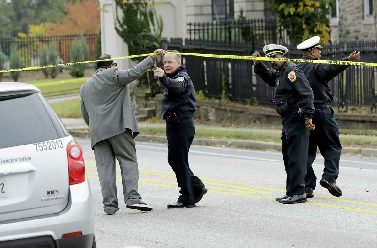 Baltimore Police Department commissioner Kevin Davis, second from left, approaches the scene of an early morning fatal collision between a school bus and a commuter bus in Baltimore, Tuesday, Nov. 1, 2016. Baltimore police spokesman T.J. Smith said the school bus rear ended a car Tuesday morning, then struck a pillar at a cemetery and veered into oncoming traffic, hitting the Maryland Transit Administration bus on the driver's side.