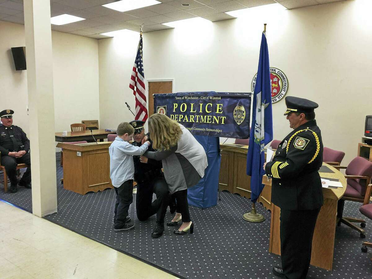 Family members participate in the promotion ceremony by helping with the officer's pin on his uniform.