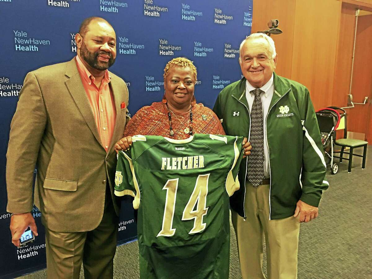 From left, Michael Fletcher, Carolyn Fletcher and Tom Marcucci pose with Jerrell Fletcher's Notre Dame-West Haven football jersey.