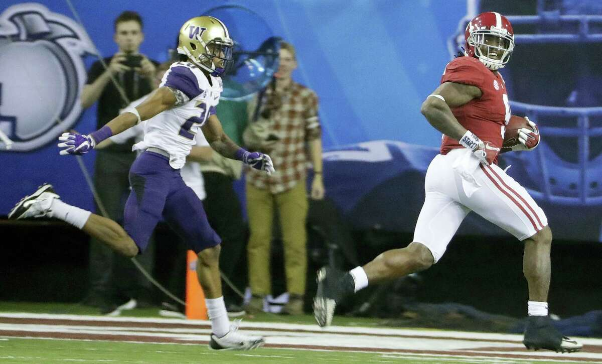 Alabama running back Bo Scarbrough (9) looks back as he runs for a touchdown against Washington during the second half of the Peach Bowl Saturday in Atlanta.