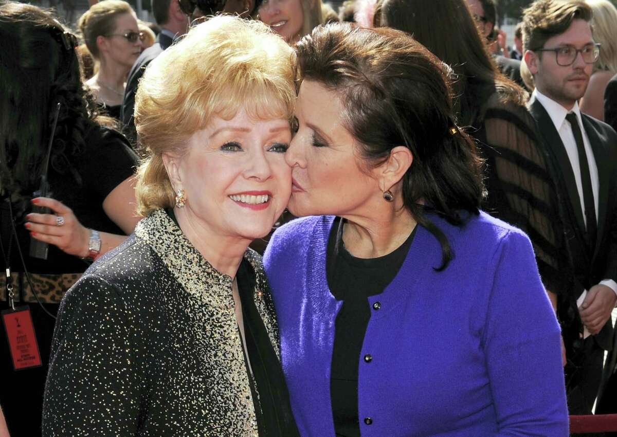 In this Sept. 10, 2011, file photo, Carrie Fisher kisses her mother, Debbie Reynolds, as they arrive at the Primetime Creative Arts Emmy Awards in Los Angeles. On Friday, Dec. 30, 2016, Reynolds' son, Todd Fisher, says his mother and sister will have a joint funeral and will be buried together at Forest Lawn Memorial Park cemetery in Los Angeles.