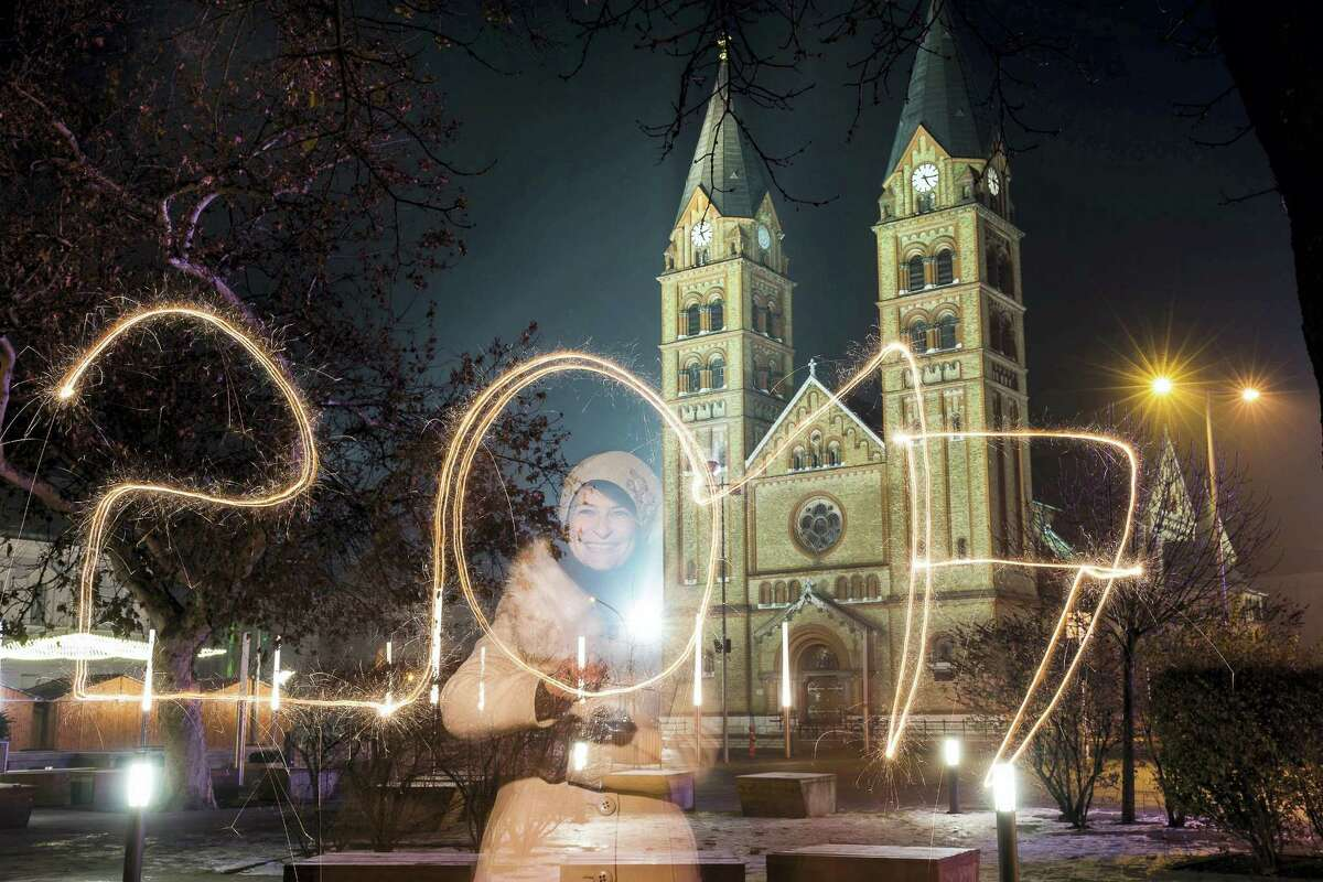 """A young woman writes """"2017"""" using a sparkler during the New Year's Eve celebrations in Nyiregyhaza, 245 kms east of Budapest, Hungary, Saturday, Dec. 31, 2016."""
