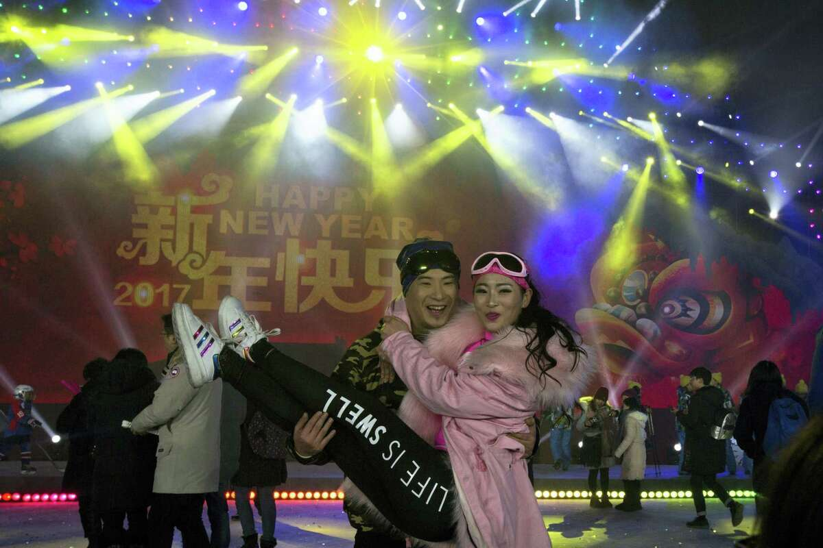 A man and a woman pose for photos after the countdown to the New Year at an event in Beijing, China, Sunday, Jan. 1, 2017.