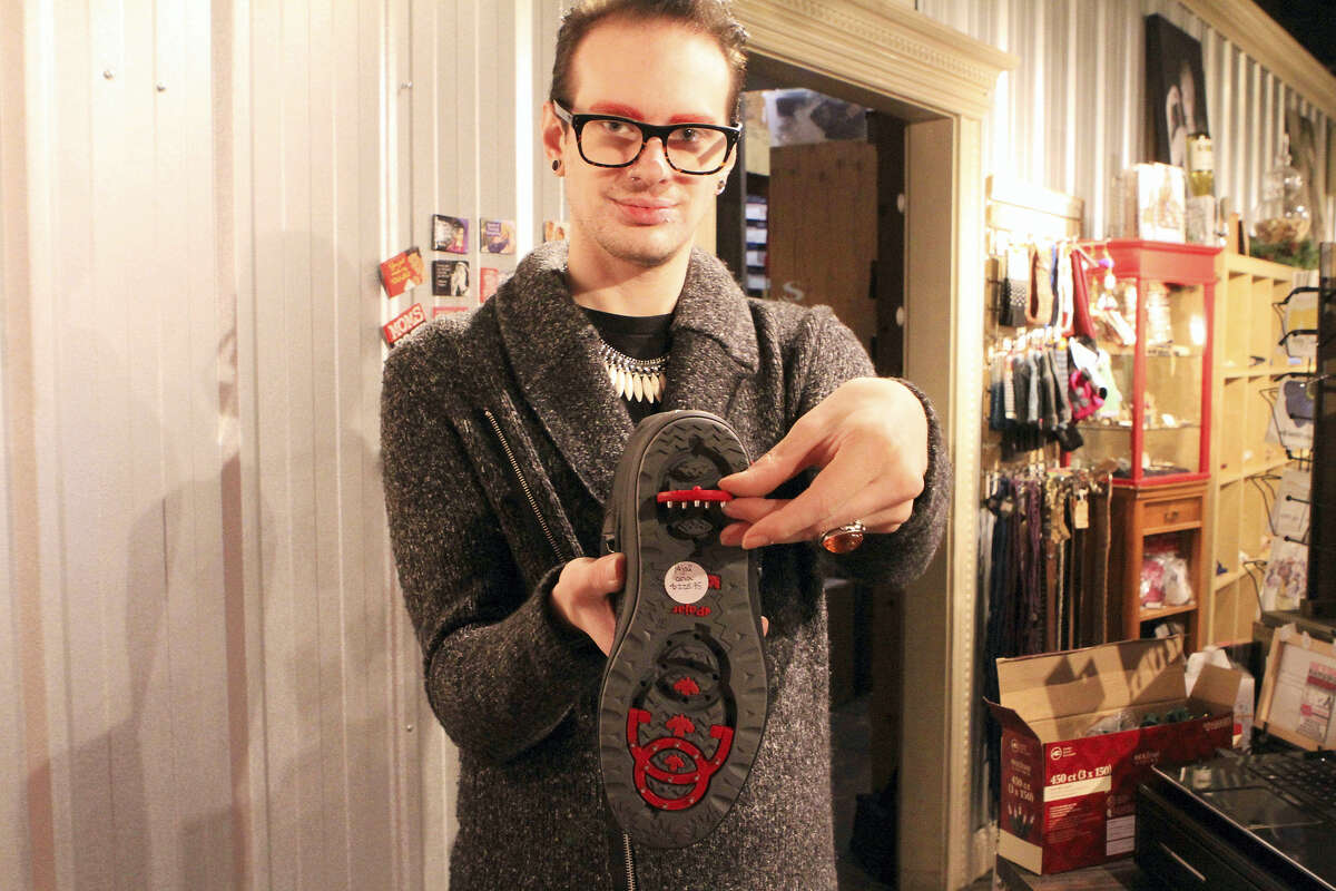 Tyler Johnson, a sales associate at ShuzyQ boutique, demonstrates a boot by Pajar with hinged inserts on the bottom containing studs that can be flipped out to walk on ice in Anchorage, Alaska.