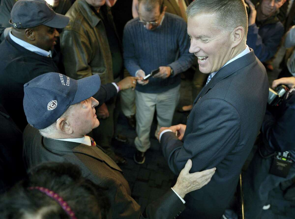 Randy Edsall talks with fan Milton Porter of Hebron, left, after a Friday's news conference.