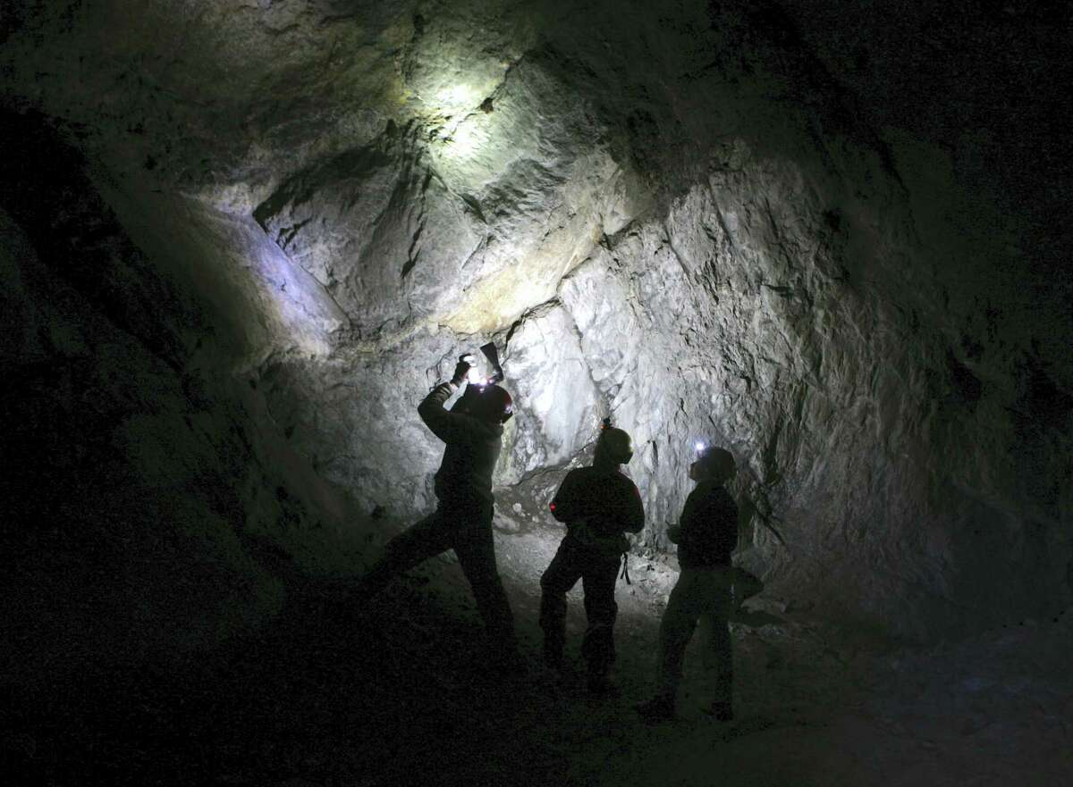 """FILE - In this Jan. 27, 2009 file photo, Ryan von Linden, left, photographs hibernating bats in an abandoned mine, while Dennis Wischman, center, and Lisa Masi take notes in Rosendale, N.Y. Biologists feared some bat species would become extinct when the mysterious """"white-nose"""" fungus was first noticed in some caves in upstate New York. The populations of little browns appear to have stabilized in some locations in upstate New York and Vermont, the region where dead bats were found starting in 2006."""