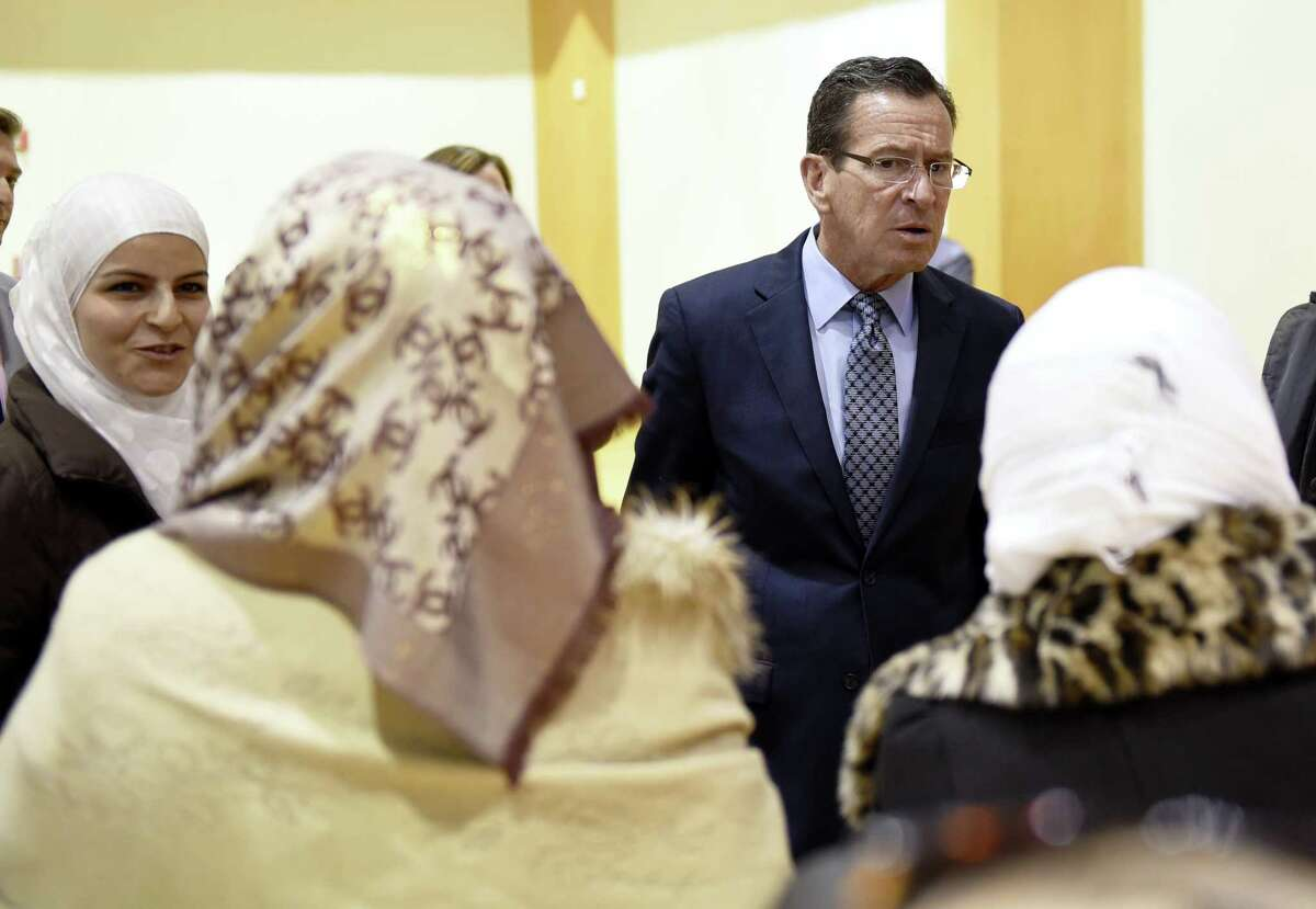 Connecticut Gov. Dannel P. Malloy listens to two Syrian refugees during a refugee celebration event at the Jewish Community Center of Greater New Haven in November. Malloy has said he'll sue if the Trump administration tries to withhold federal funds to New Haven and other so-called sanctuary cities that refuse to cooperate with federal immigration officials.