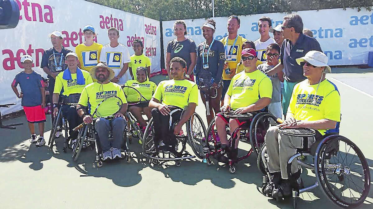 David Kelly, middle row left, Carlos Quiles, front row middle, and other members of the Gaylord Hospital Sports Association pose with women tennis players Raquel Atawo and Abigail Spears.