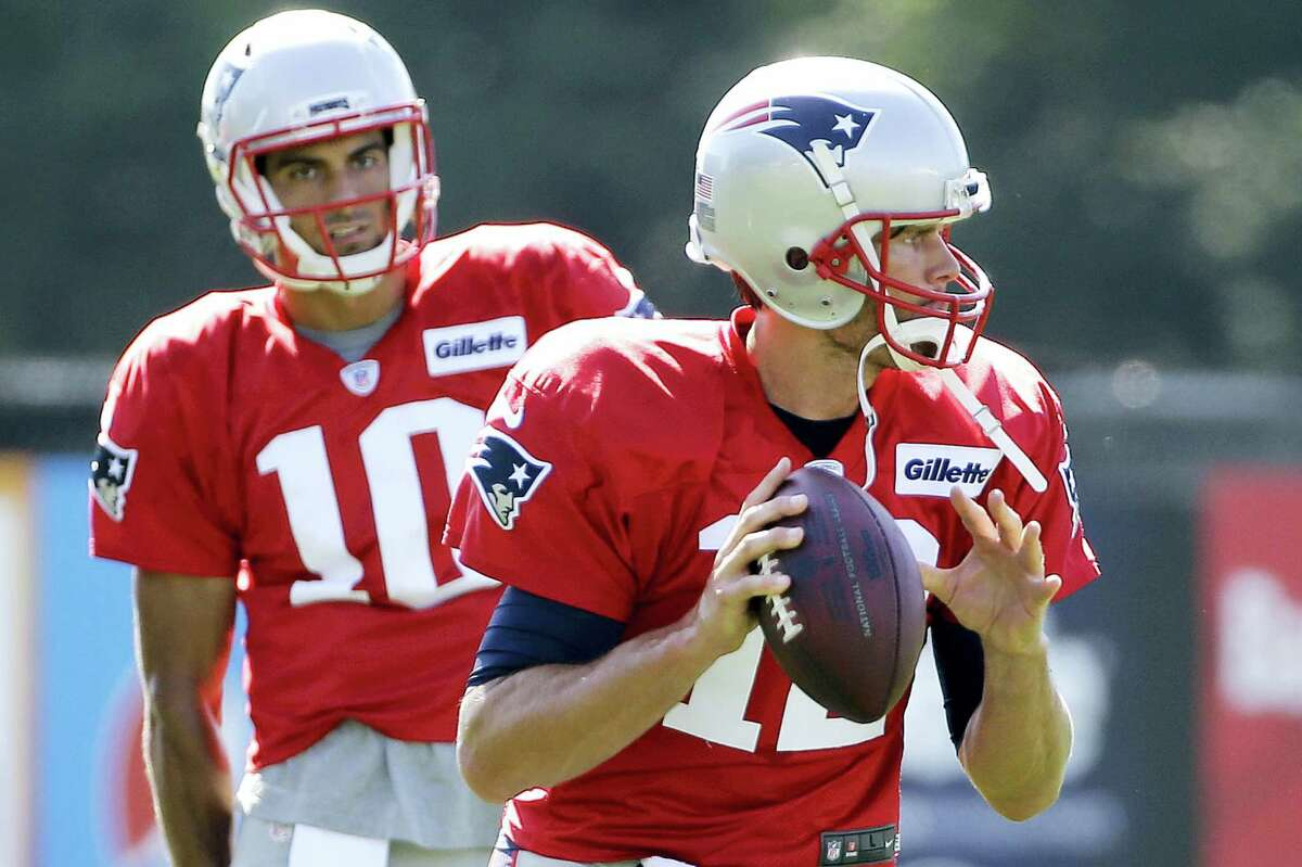 In this Aug. 9, 2016 photo, New England Patriots quarterback Tom Brady (12) gets set to throw a pass as quarterback Jimmy Garoppolo (10) watches during NFL football training camp in Foxborough, Mass.