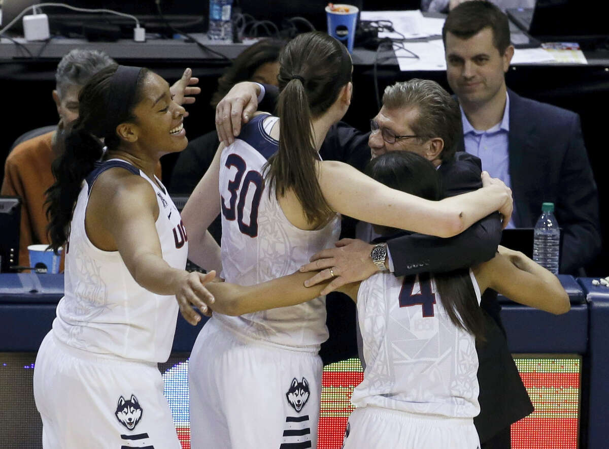 Connecticut head coach Geno Auriemma hugs Morgan Tuck (3) Moriah Jefferson (4) and Breanna Stewart (30) following the championship game against Syracuse at the women's Final Four in the NCAA college basketball tournament Tuesday, April 5, 2016, in Indianapolis. Connecticut won 82-51. (AP Photo/Darron Cummings)
