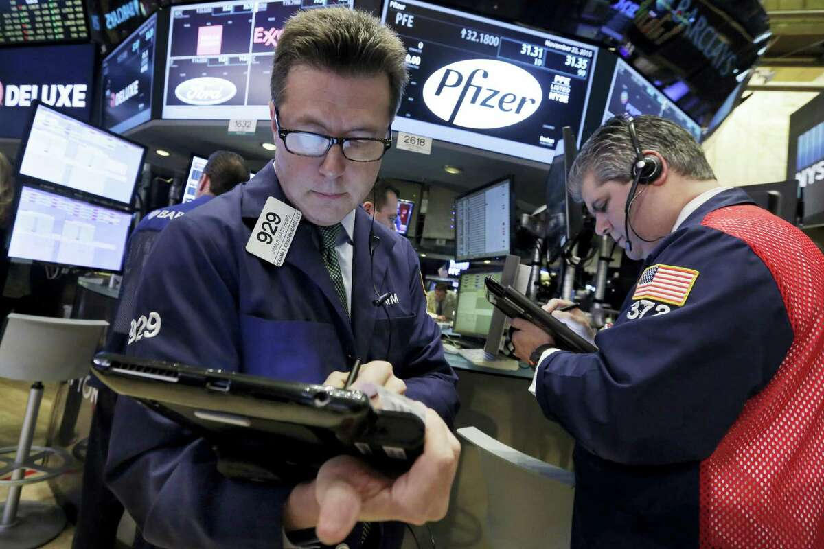 """In this Nov. 23, 2015 photo, traders James Matthews, left, and John Panin work at the post that handles Pfizer, on the floor of the New York Stock Exchange. Allergan and Pfizer on Wednesday, April 6, 2016 called off a record $160 billion merger after the Treasury issued new rules to make """"tax inversions"""" less lucrative."""