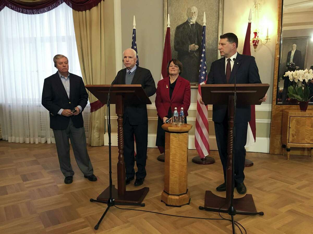 Latvian President Raimonds Vejonis, right, looks at US Sen. John McCain centre left, during a press conference, Wednesday, Dec. 28, 2016 in Riga, Latvia, while Lindsey Graham, R-SC., and Amy Klobuchar, D-Minn., stand in the background. Russia can expect hard-hitting sanctions from United States lawmakers if an investigation proves that Moscow interfered in the presidential election, a U.S. senator said Wednesday during a visit to Latvia. (AP Photo/Vitnija Saldava)