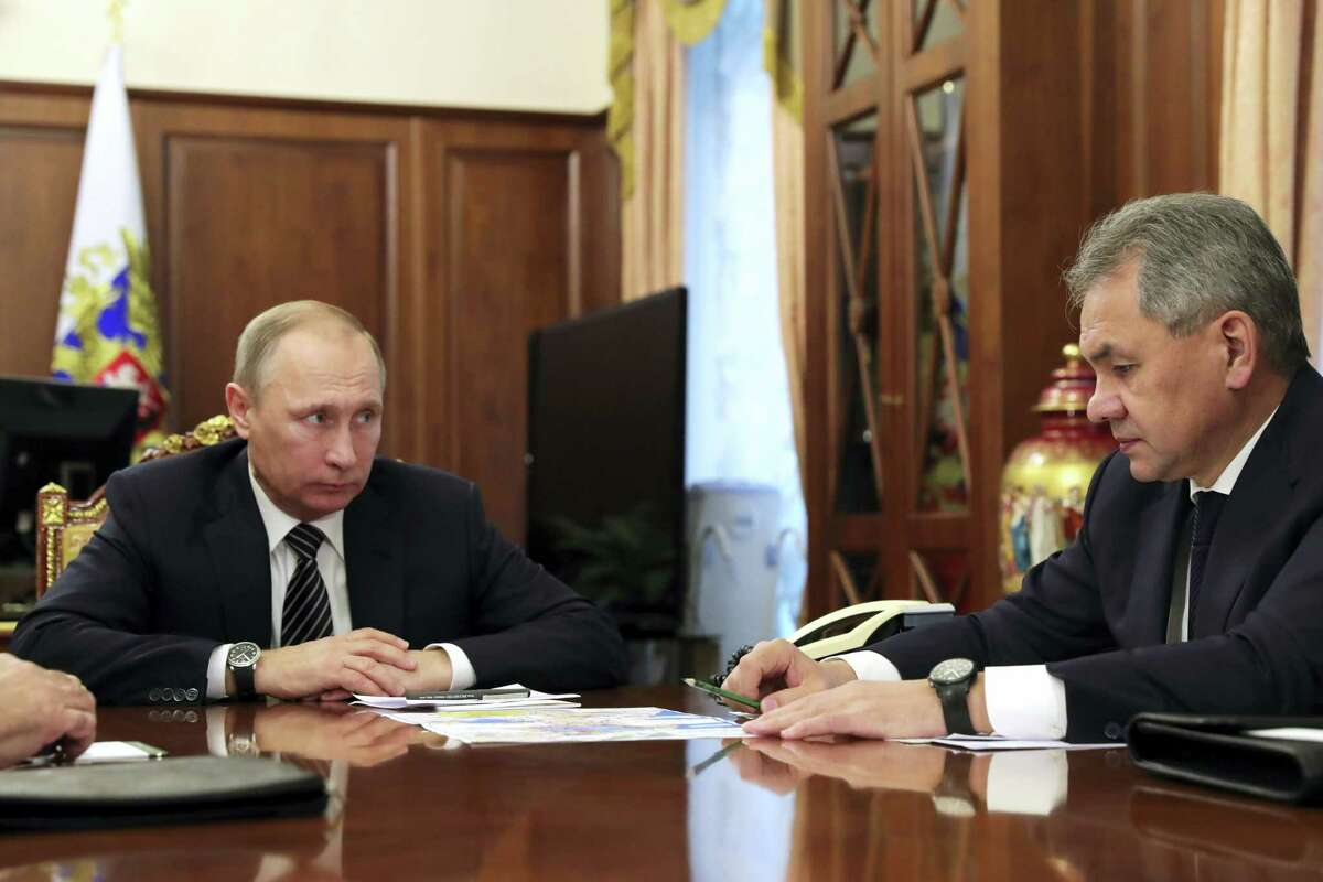 Russian President Vladimir Putin, left, listens to Defense Minister Sergei Shoigu in Moscow on Thursday. Putin is ordering to scale down the Russian military presence in Syria. Putin made the statement Thursday while declaring that a cease-fire in Syria brokered by Russia and Turkey will start at midnight.